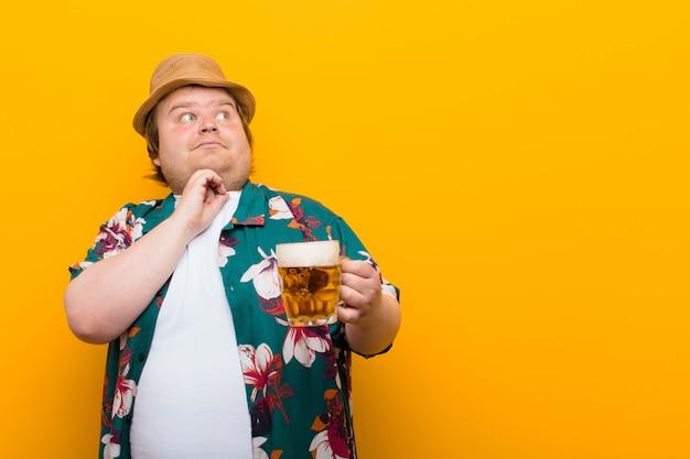 ビールのパイントを持つ若い大きなサイズの男