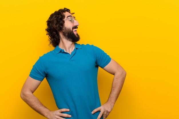 Молодой сумасшедший мужчина смотрит счастливым, веселым и уверенным, гордо улыбается и смотрит в бок обеими руками на бедра