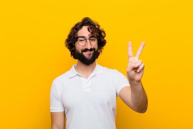 Молодой сумасшедший человек улыбается и смотрит дружелюбно, показывая номер два или секунду рукой вперед, считая