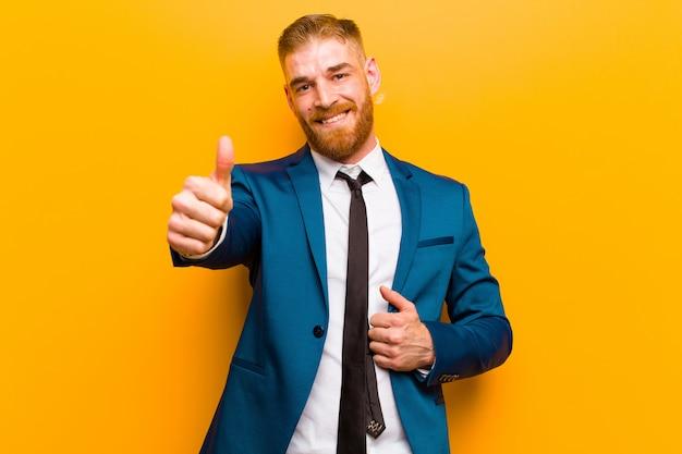 自信を持って、屈託のない、自信を持って、幸せな、オレンジの親指で積極的に笑顔を感じて若い赤い頭の実業家