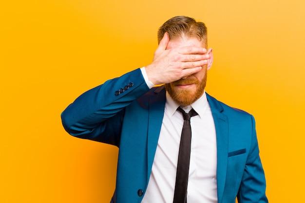 片手で怖がって、不思議に思っているか、盲目的に驚きのオレンジを待っている目を覆っている若い赤い頭の実業家