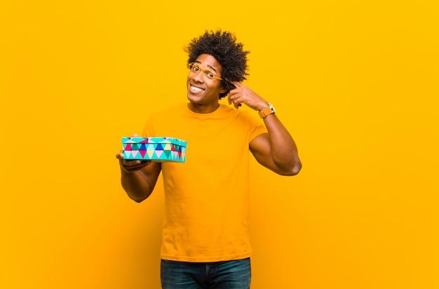 Молодой афроамериканец человек с подарочной коробке оранжевый фон