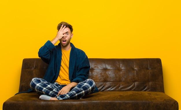 パジャマを着た若い男はショックを受け、怖がって、顔を手で覆い、指の間を覗きます。ソファに座って