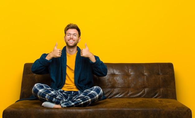 両方の親指で、広く幸せ、肯定的、自信を持って成功を探して笑顔のパジャマを着た若い男。ソファに座って