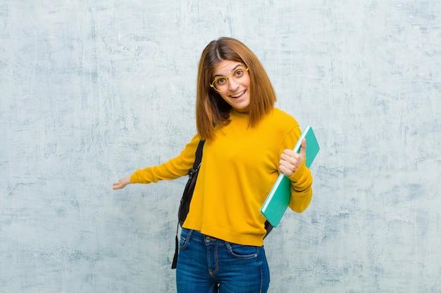 Молодой студент женщина выглядит счастливой, высокомерной, гордой и самодовольной, чувствуя себя гранж номер один стена