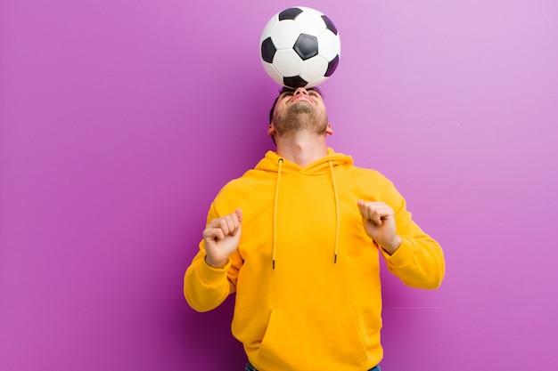 Молодой испанец человек с футбольным мячом фиолетовый
