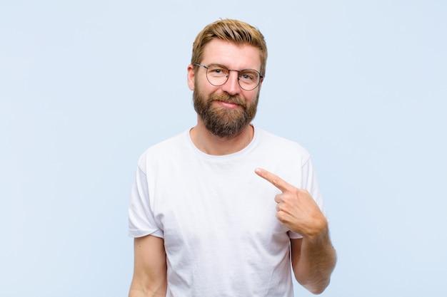 誇りに思って、自信を持って、幸せ、笑みを浮かべて、自作のナンバーワンサインを指している若い金髪の成人男性