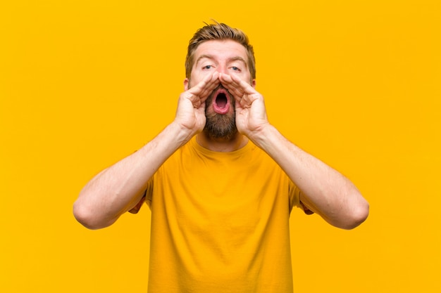 Молодой блондин, чувствуя себя счастливым, возбужденным и позитивным, громко крича руками возле рта, взывая к оранжевой стене