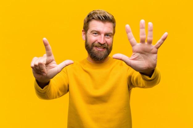 Молодой блондин человек улыбается и выглядит дружелюбно, показывая номер семь седьмой с рукой вперед, считая вниз оранжевую стену