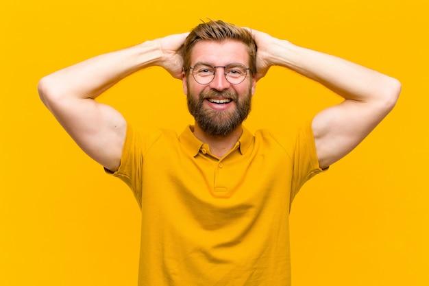 肯定的な態度のオレンジ色の壁で、幸せと屈託のない、フレンドリーでリラックスした生活と成功を楽しんでいる若いブロンドの男