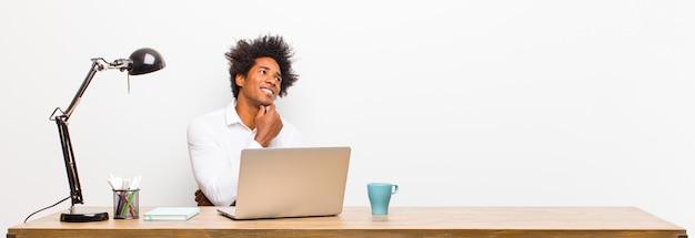 幸せな笑顔と空想や疑い、机の上の側にいる若い黒人実業家