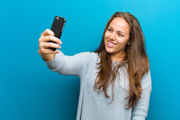 携帯電話の青を持つ若い女性