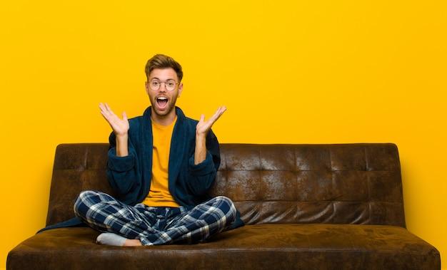 幸せで興奮しているように見えるパジャマを着た若い男は、顔の隣に両手を開いて予期せぬ驚きにショックを受けました。ソファに座って