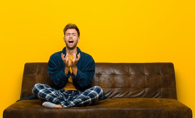 絶望的で欲求不満、ストレス、不幸、イライラ、叫び、悲鳴を上げるパジャマを着ている若い男。ソファに座って