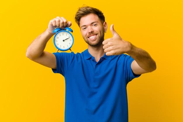 オレンジ色の目覚まし時計と若い男