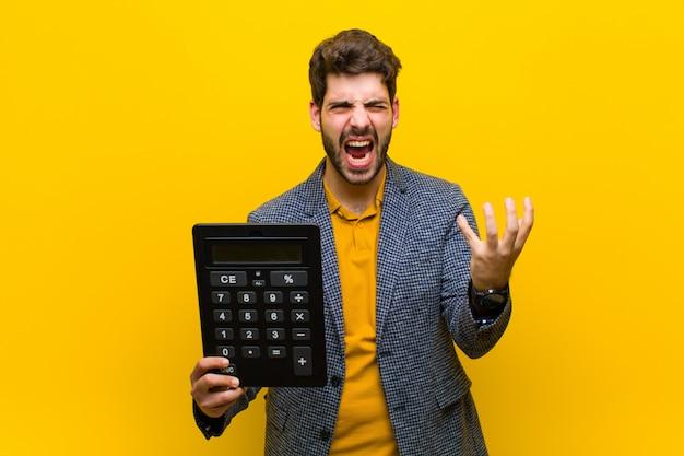 オレンジ電卓で若いハンサムな男