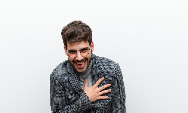 若いマネージャーの男はショックを受けて驚いた、笑顔、心に手をとって、幸せになり、感謝の気持ちを示す白い壁