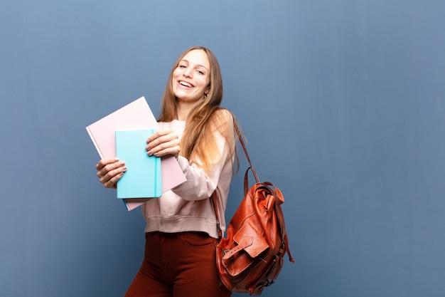 若い可愛い本と学生の女性とコピースペースを持つ青い壁のバッグ