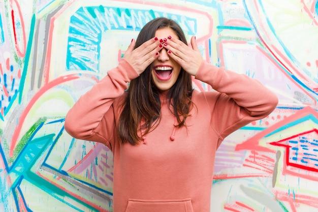笑顔で幸せを感じ、両手で目を覆い、信じられないほどの驚きを待つ