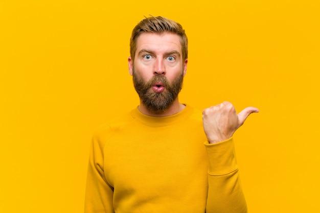 信じられないことに驚いた若いブロンドの男、側のオブジェクトを指して、すごい、信じられないほどのオレンジ色の壁を言って