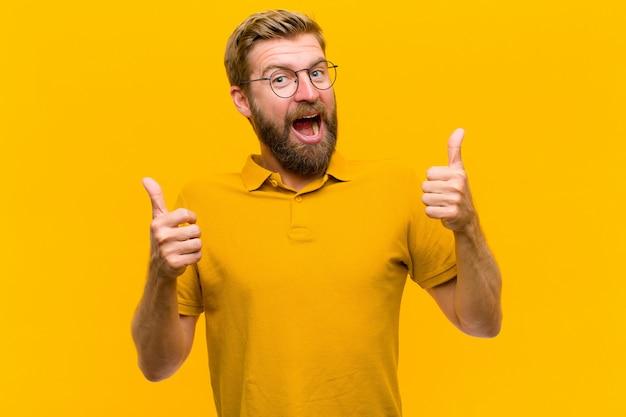 Молодой блондин человек, широко улыбаясь, выглядит счастливым, позитивным, уверенным и успешным, с большими пальцами вверх по оранжевой стене