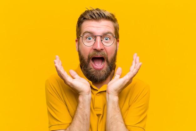 予期せぬ驚きのオレンジ色の壁のためにショックと興奮、笑い、驚きと幸せを感じている若いブロンドの男