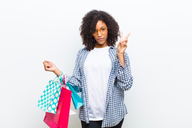 ショッピングバッグの白い壁を持つ若いかなり黒人女性