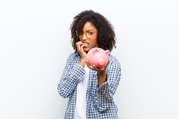 貯金箱の白い壁を持つ若いかなり黒人女性