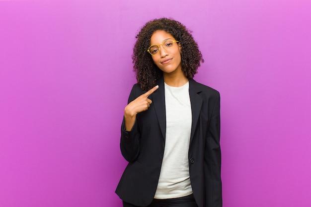 誇りに思って、自信を持って、幸せ、笑みを浮かべて、自己を指すまたはナンバーワンのサインを作る若い黒人ビジネス女性