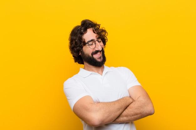 Молодой сумасшедший юноша счастливо смеется со скрещенными руками, в расслабленной, позитивной и довольной позе желтой стены