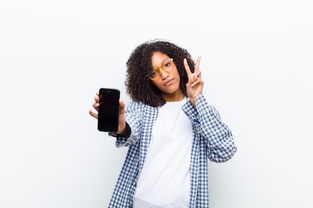 Молодая красивая чернокожая женщина со смартфоном на белой стене