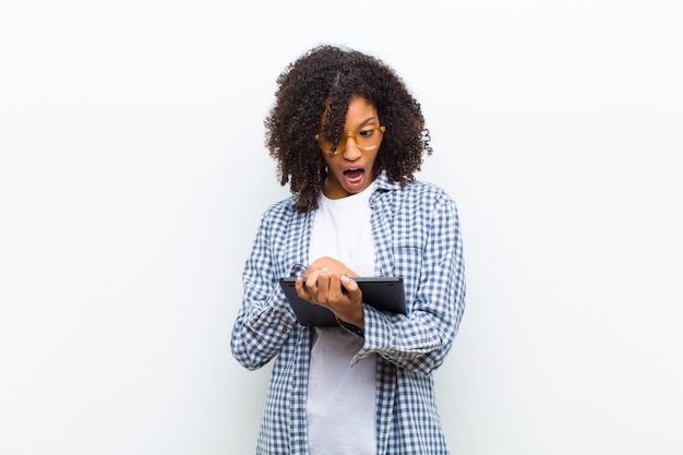 スマートタブレットの白い壁を持つ若いかなり黒人女性