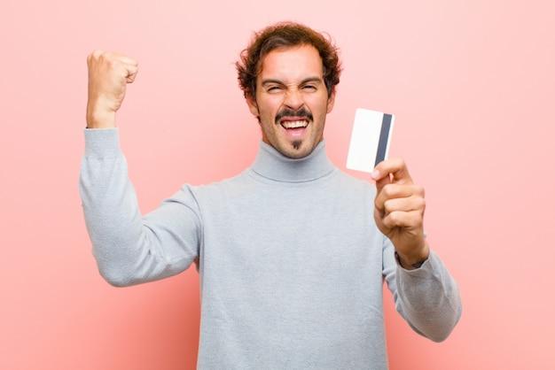 クレジットカードピンクの平らな壁を持つ若いハンサムな男