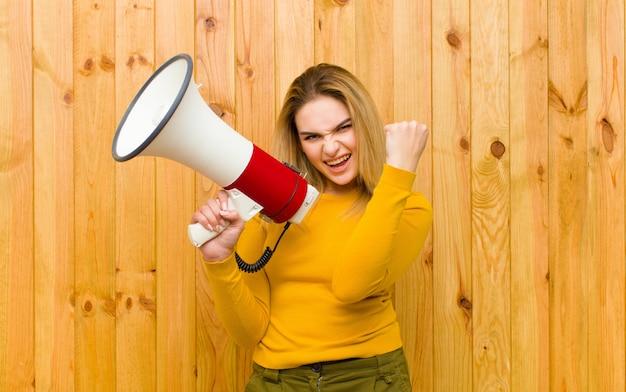 Молодая милая белокурая женщина с деревянной стеной мегафона