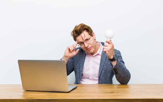 Молодой красный головной бизнесмен работая в его столе имея идею