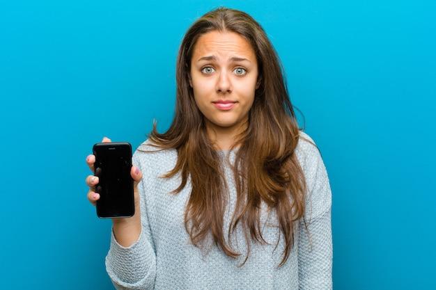 Молодая женщина с мобильным телефоном против сини