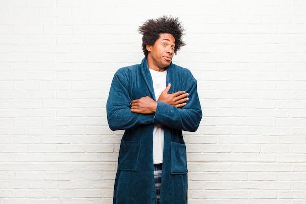 Молодой темнокожий мужчина в пижаме с платьем пожимает плечами, чувствуя смущение и неуверенность, сомневаясь со скрещенными руками и озадаченным взглядом на кирпичную стену