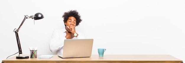 喉の痛みやインフルエンザの症状で病気を感じている若い黒の実業家が口で咳