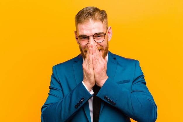 Молодой рыжий бизнесмен счастлив и взволнован удивлен и поражен охватывающий рот руками, хихикающими с милым выражением на оранжевом фоне