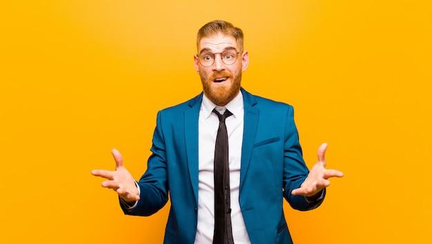 Молодой рыжий бизнесмен, чувствуя себя крайне потрясенным и удивленным, взволнованным и паниковавшим с подчеркнутым и испуганным взглядом на оранжевом фоне