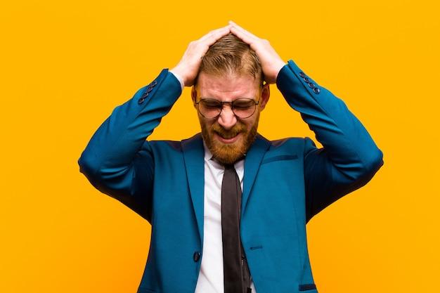 オレンジ色の背景に対して片頭痛と不幸な疲れを感じて頭に手を上げてイライラした若い赤ヘッド実業家