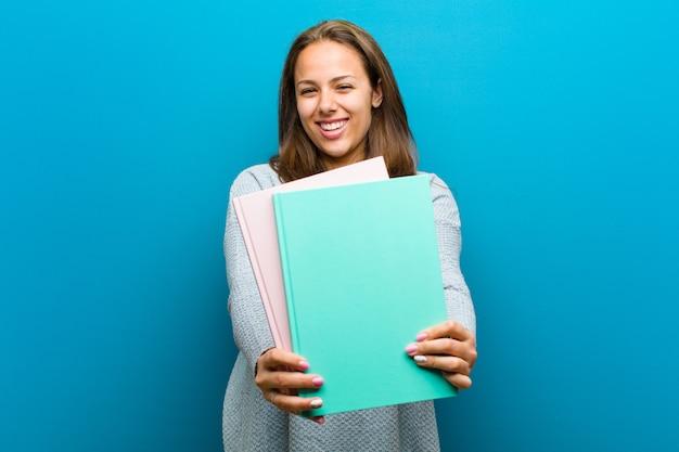青い背景のノートを持つ若い女性