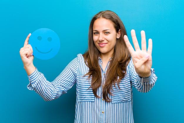 青い背景にスマイリーの顔を持つ若い女性