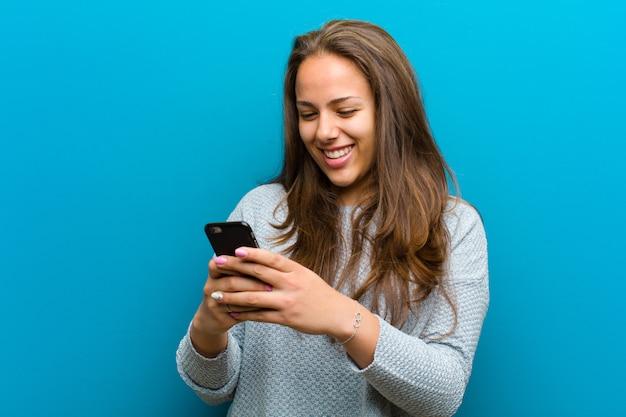 青い背景の携帯電話を持つ若い女性
