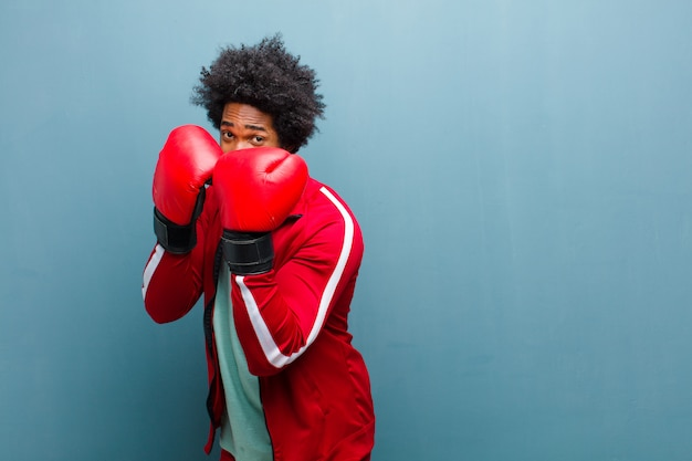Молодой черный человек с боксерскими перчатками против синей стены гранж
