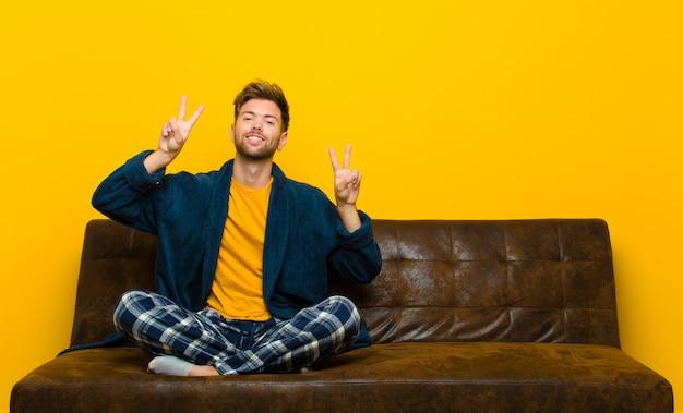 笑顔で幸せなフレンドリーで満足しているジェスチャーの勝利または両手で平和を探してパジャマを着ている若い男。ソファに座って