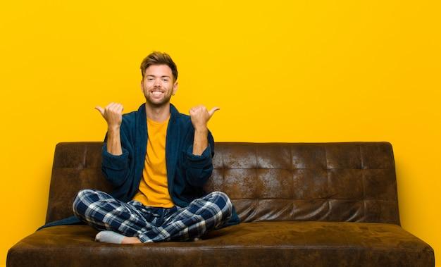 若い男がパジャマを身に着けて喜んで笑って、両方の親指で屈託のない肯定的な幸せな気持ちを探しています。ソファに座って