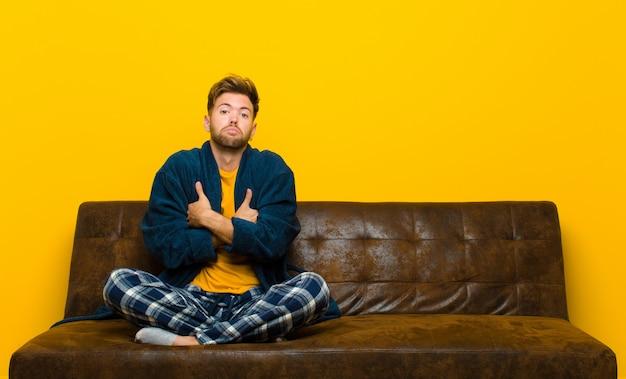 腕を組んで混乱した表情で混乱し不確実な疑いを感じながら肩をすくめているパジャマを着た若い男。ソファに座って
