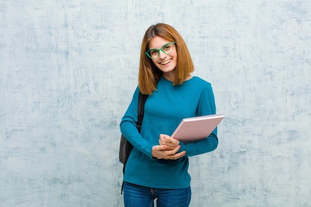フレンドリーで前向きだが不安な態度で内気に、元気に笑っている若い学生女性