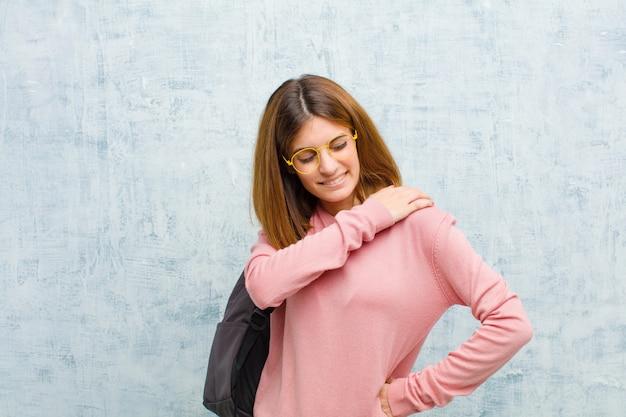 疲れている若い学生女性は、背中や首の痛みに悩まされてイライラして落ち込んでいるストレスを強調しました。
